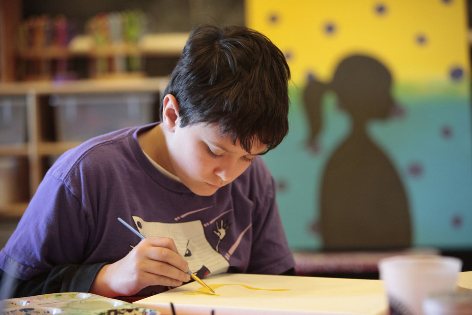 Left: Jonathan Jones, 10, works on his painting at the Edmond Parks and Recreation Department's spring break art camp.