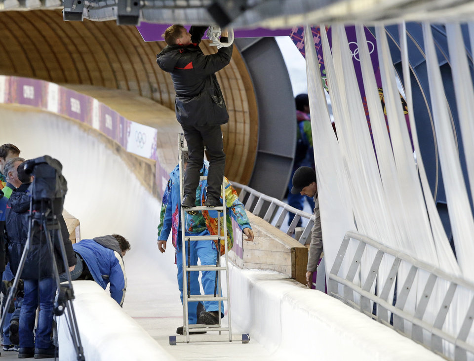 A track worker repairs some lights that were damaged after a worker was hit by a forerunner bobsled just before the men\'s two-man bobsled training at the 2014 Winter Olympics, Thursday, Feb. 13, 2014, in Krasnaya Polyana, Russia. (AP Photo/Dita Alangkara)