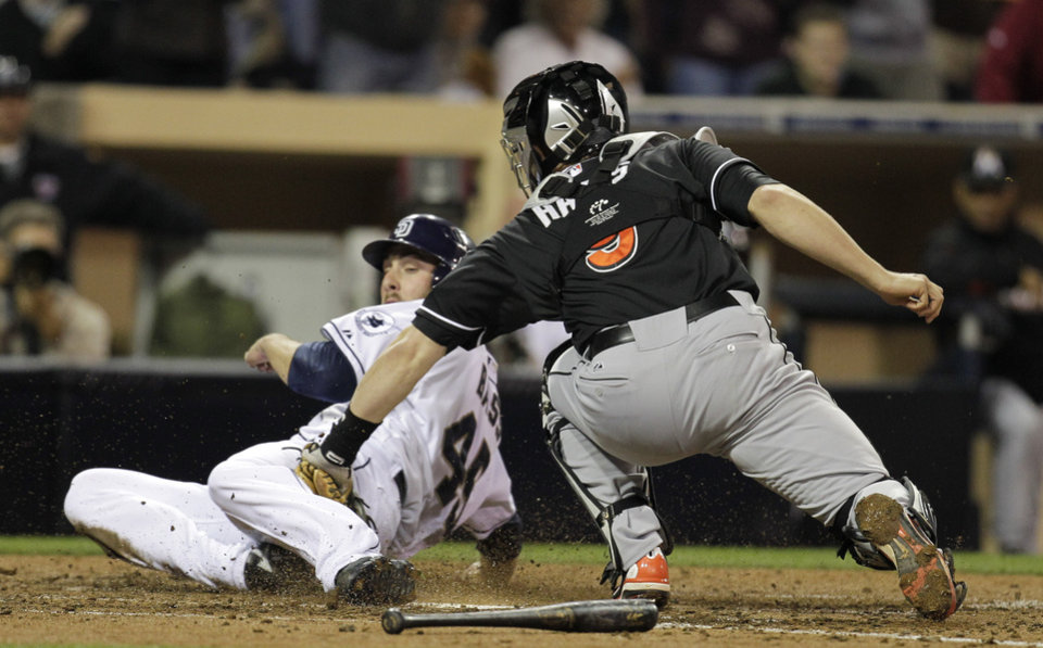 Photo -   Miami Marlins catcher Brett Hayes, right, is late with the tag on San Diego Padres' Anthony Bass, left, as he slides in safely to home off a hit by Mark Kotsay in the fifth inning during their baseball game Friday, May 4, 2012, in San Diego. (AP Photo/Gregory Bull)