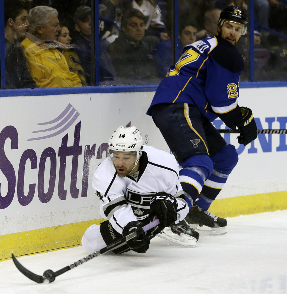 Photo - Los Angeles Kings' Justin Williams, bottom, passes the puck as he falls while St. Louis Blues' Alex Pietrangelo watches during the first period of an NHL hockey game, Thursday, Jan. 16, 2014, in St. Louis. (AP Photo/Jeff Roberson)