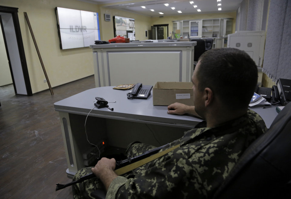 Photo - A pro-Russian fighter sits at the duty department of the captured Interior Ministry headquarters in Donetsk, eastern Ukraine Tuesday, July 1, 2014. The rebels captured the Interior Ministry headquarters in the city after an hours-long gun battle, a day after the president said rebels weren't serious about peace talks and ended a cease-fire. (AP Photo/Dmitry Lovetsky)