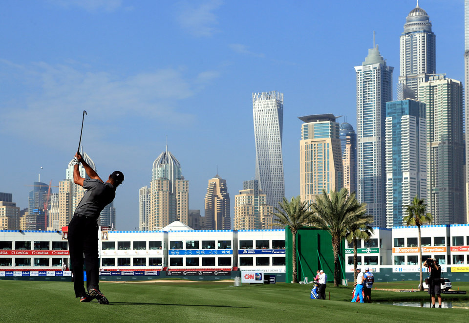 Photo - Tiger Woods from the U.S. follows through a shot on the 18th hole during the first round of the Dubai Desert Classic golf tournament in Dubai, United Arab Emirates, Thursday, Jan. 30, 2014. (AP Photo)