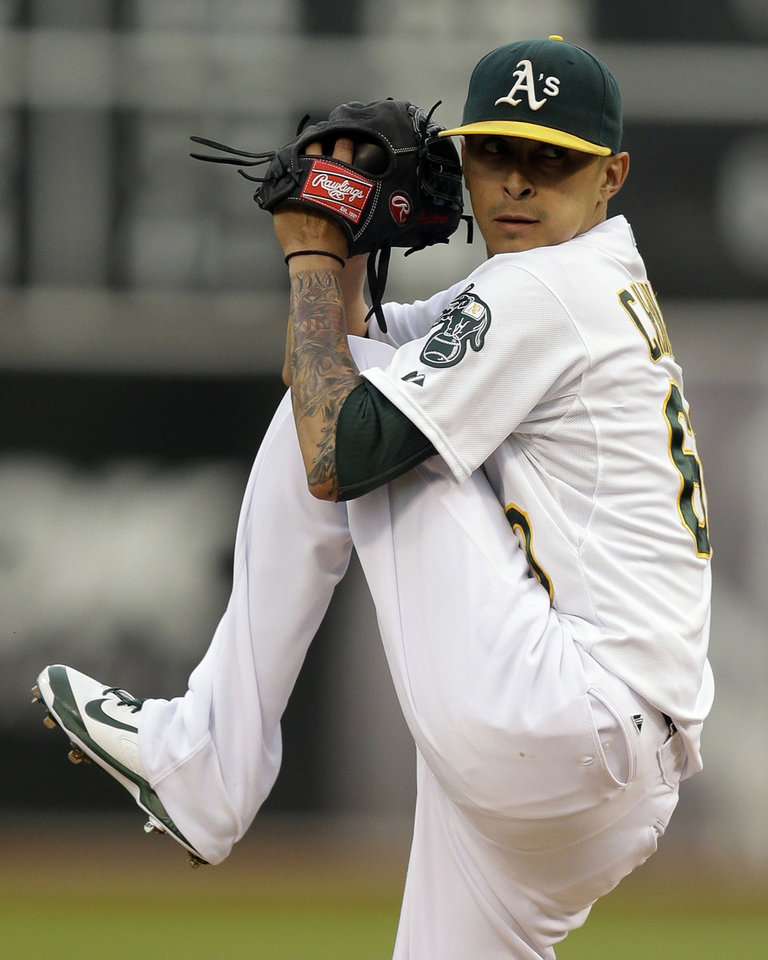 Photo - Oakland Athletics' Jesse Chavez works against the San Francisco Giants in the first inning of a baseball game Monday, July 7, 2014, in Oakland, Calif. (AP Photo/Ben Margot)