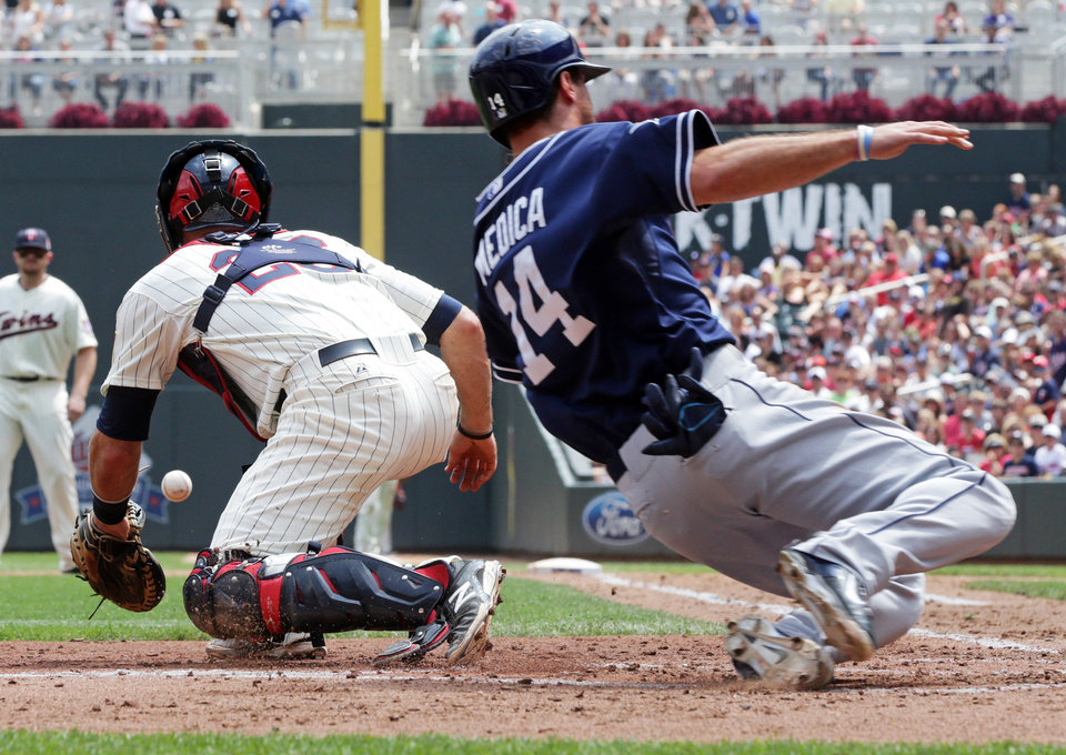 Photo - Minnesota Twins catcher Eric Fryer, left, waits for the throw as San Diego Padres' Tommy Medica scores on a double by Jedd Gyorko off Minnesota Twins pitcher Kevin Correia in the fourth inning of a baseball game, Wednesday, Aug. 6, 2014, in Minneapolis. (AP Photo/Jim Mone)