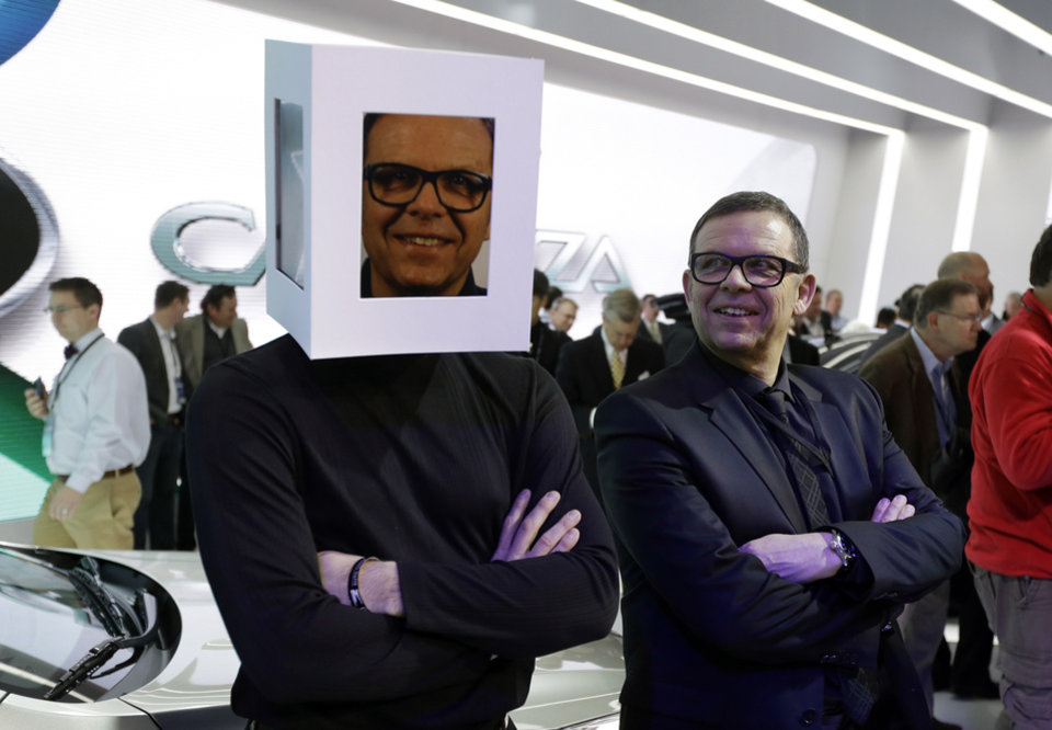 Peter Schreyer, right, President and Chief Design Officer for Kia Motors looks towards a model sporting a video images of himself at the Kia unveiling during the North American International Auto Show in Detroit, Tuesday, Jan. 15, 2013. (AP Photo/Carlos Osorio)