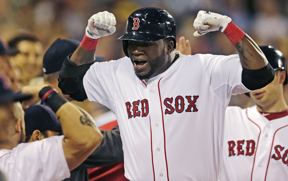 Photo - Boston Red Sox designated hitter David Ortiz s congratulated by teammates after his three-run home run against the Cleveland Indians during the third inning of a baseball game at Fenway Park in Boston, Thursday, May 23, 2013. (AP Photo/Charles Krupa)