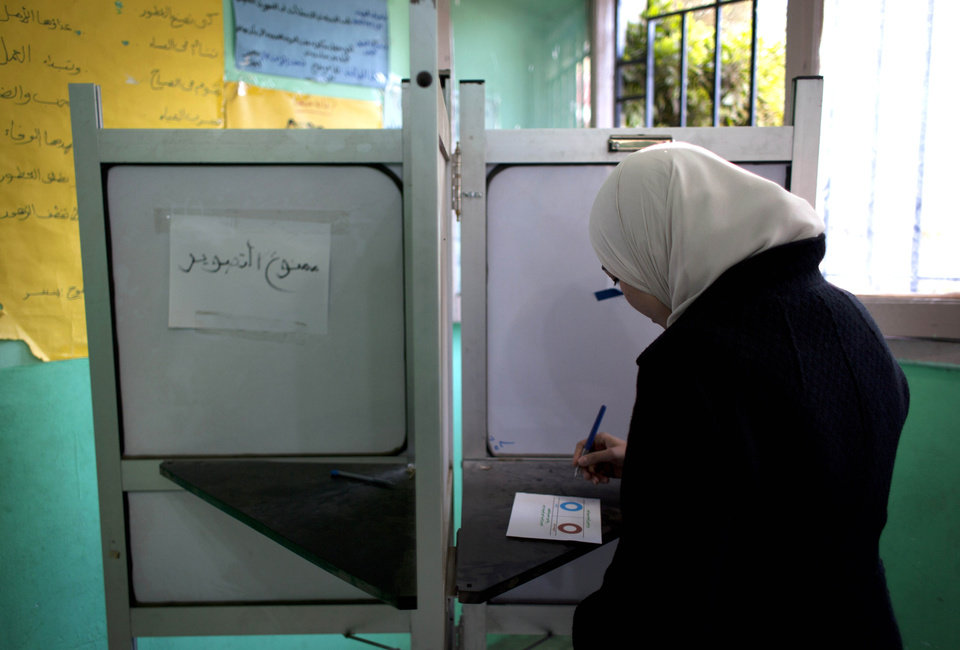 An Egyptian woman votes at a polling station in the second round of a referendum on a disputed constitution drafted by Islamist supporters of president Mohammed Morsi, in Giza, Egypt, Saturday, Dec. 22, 2012. (AP Photo/Nasser Nasser)