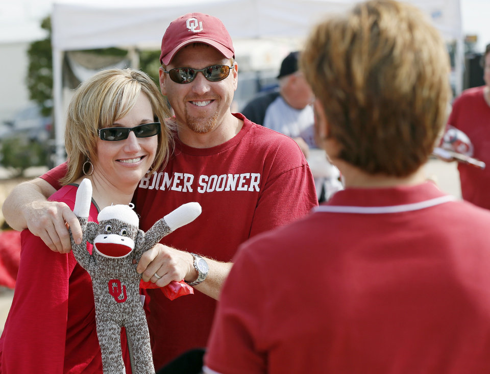 Photo - OU fans Angela Marsee and Bobby Marsee of Weatherford, Okla., pose with an OU sock monkey as Jody Wilham of Oklahoma City takes a picture during the Bevo Bash, an event for fans traveling to OU-Texas, in Marietta, Okla., Friday, Oct. 12, 2012. The University of Oklahoma Sooners and the University of Texas Longhorns will play the Red River Rivalry college football game in Dallas on Saturday. Photo by Nate Billings, The Oklahoman