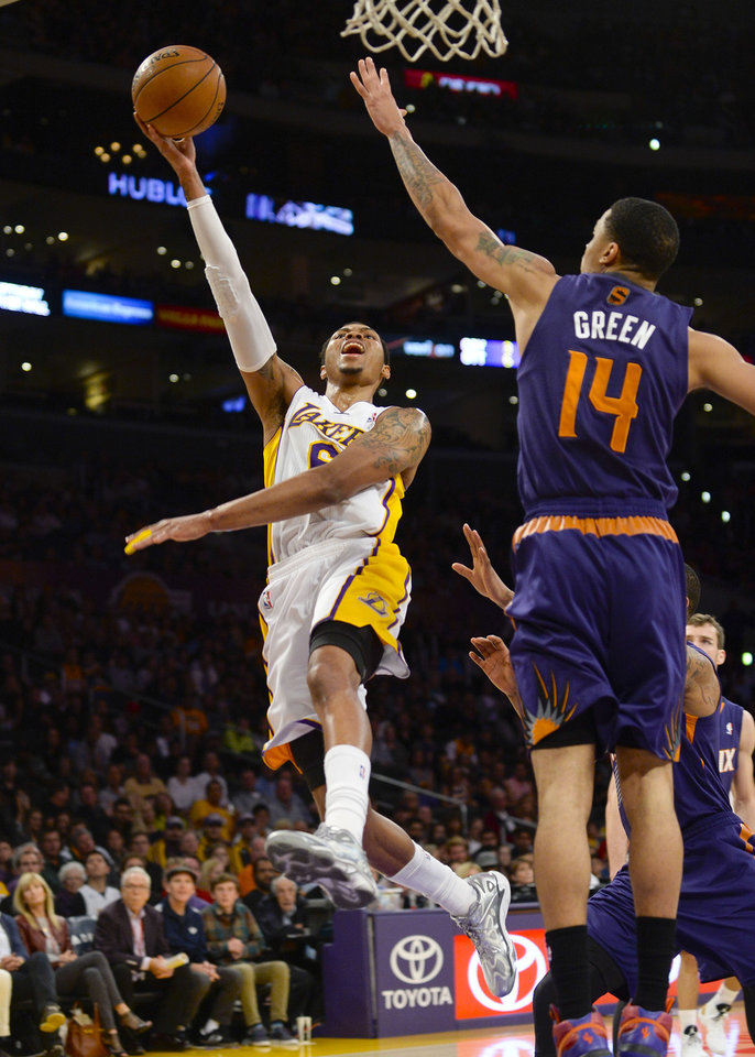 Photo - Los Angeles Lakers guard Kent Bazemore (6) drive on Phoenix Suns guard Gerald Green (14) for a basket on a fast break in the first half of an NBA basketball game, Sunday, March 30, 2014, in Los Angeles.(AP Photo/Gus Ruelas)