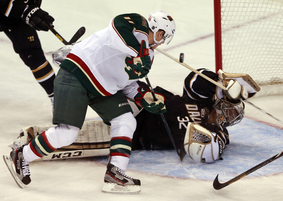 Photo - Minnesota Wild left wing Zach Parise (11) scores against Dallas Stars goalie Kari Lehtonen (32) during the first period of an NHL hockey game Monday, March 25, 2013 in Dallas. (AP Photo/ Michael Mulvey)