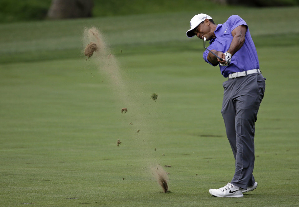 Photo - Tiger Woods hits from the fairway on the 15th hole during the first round of the PGA Championship golf tournament at Valhalla Golf Club on Thursday, Aug. 7, 2014, in Louisville, Ky. (AP Photo/John Locher)