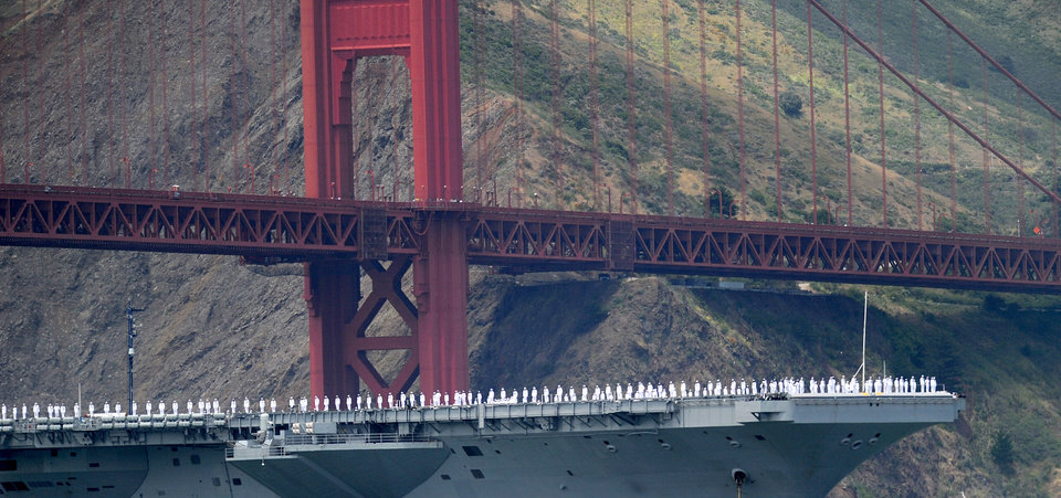 Photo -   With sailors on deck, the USS Nimitz passes beneath the Golden Gate Bridge during a celebration of the bridge's 75th anniversary on Sunday, May 27, 2012, in San Francisco. The commemoration included a vintage car show, an exhibit of roughly 1,558 pairs of shoes representing people who have committed suicide by jumping from the span, and a fireworks display slated for evening. (AP Photo/Noah Berger)