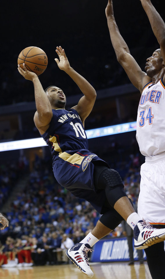 Photo - New Orleans Pelicans Eric Gordon (10) shoots in front of Oklahoma City Thunder center Hasheem Thabeet (34) in the first quarter of an NBA basketball preseason game in Tulsa, Okla., Thursday, Oct. 17, 2013. New Orleans won 105-102. (AP Photo/Sue Ogrocki) ORG XMIT: OKSO122