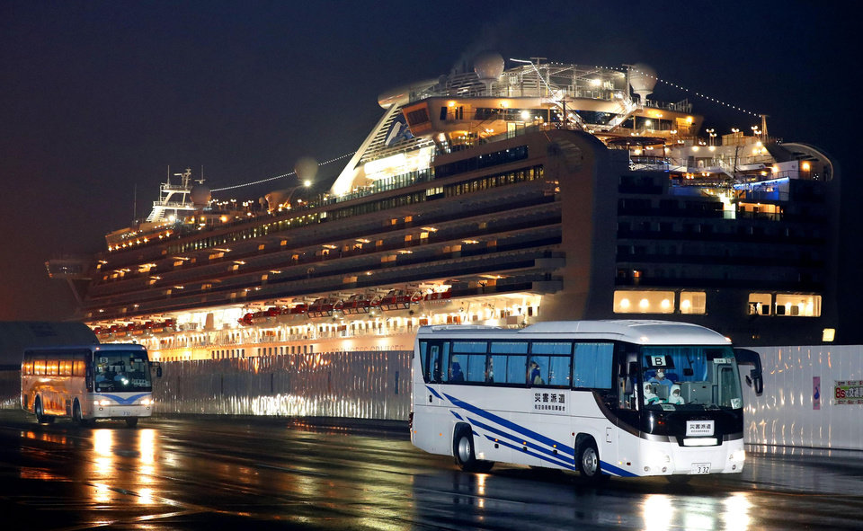 Photo -  Buses carrying U.S. passengers who were aboard the quarantined cruise ship the Diamond Princess, seen in background, leaves Yokohama port, near Tokyo, early Monday, Feb. 17, 2020. The cruise ship was carrying nearly 3,500 passengers and crew members under quarantine. (Jun Hirata/Kyodo News via AP)