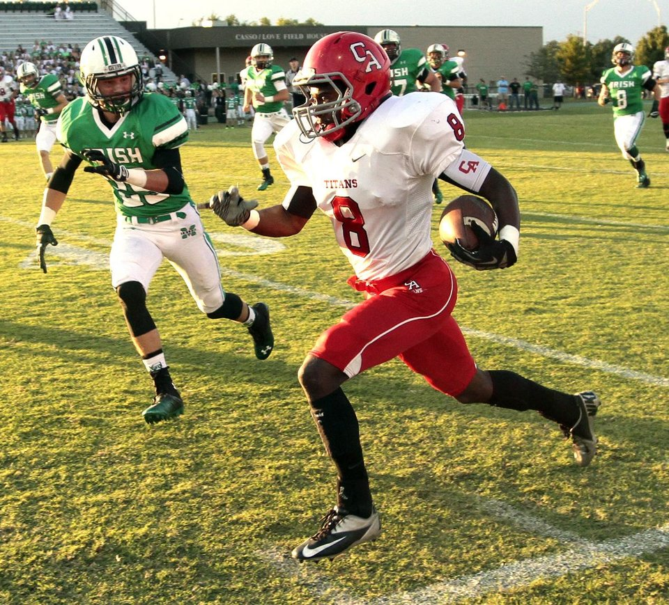 Carl Albert's Tre Bruner runs after a catch and is chased out of bounds by Chase Skelton as the Titans play the Bishop McGuinness Irish on Friday, Oct. 4, 2013 in Oklahoma City, Okla.  Photo by Steve Sisney, The Oklahoman