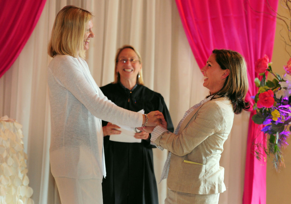 Photo - Julie Engbloom, left,  and Laurie Brown, right, get married by Judge Beth A. Allen at the Melody Ballroom, Monday, May, 19, 2014,  in Portland, Ore. Federal Judge Michael McShane released an opinion on Oregon's Marriage Equality lawsuit that grants gay and lesbian couples the freedom to marry in Oregon. (AP Photo/Steve Dykes)