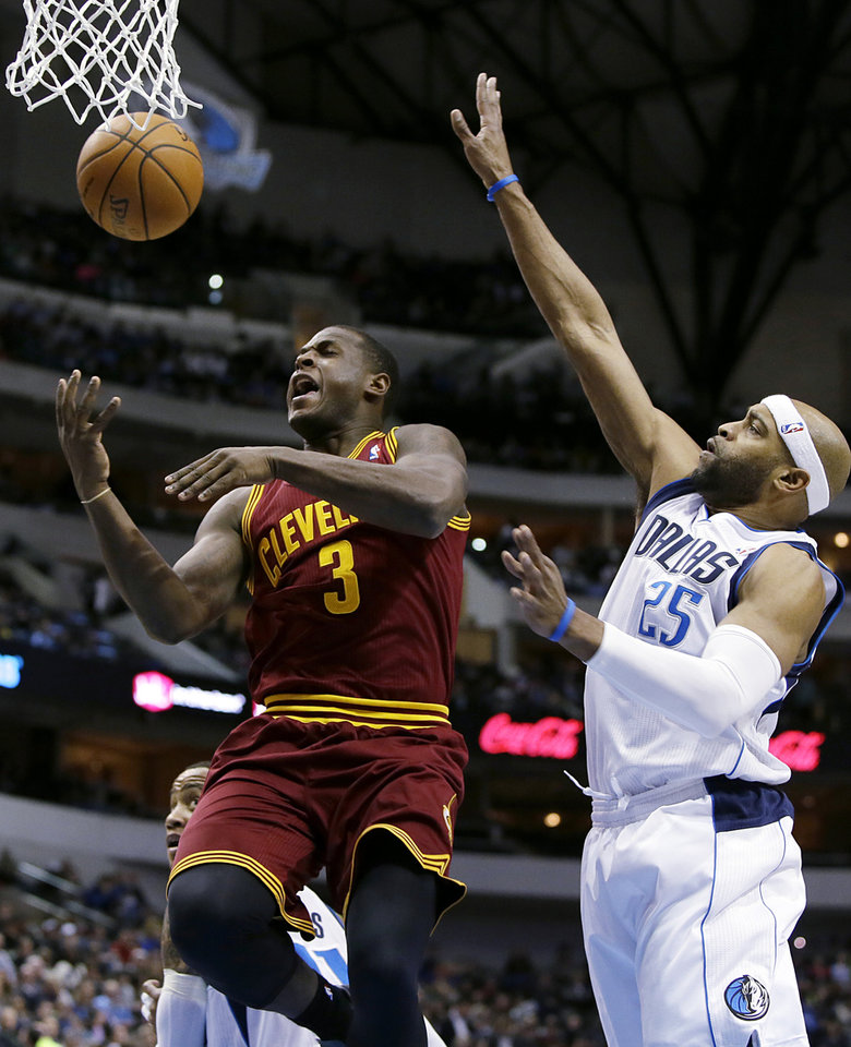 Photo - CORRECTS NAME TO DION WAITERS NOT SHANE LARKIN Cleveland's Dion Waiters (3) has the ball knocked away on a shot attempt by Dallas Mavericks' Vince Carter (25) in the first half of an NBA basketball game, Monday, Feb. 3, 2014, in Dallas. (AP Photo/Tony Gutierrez)