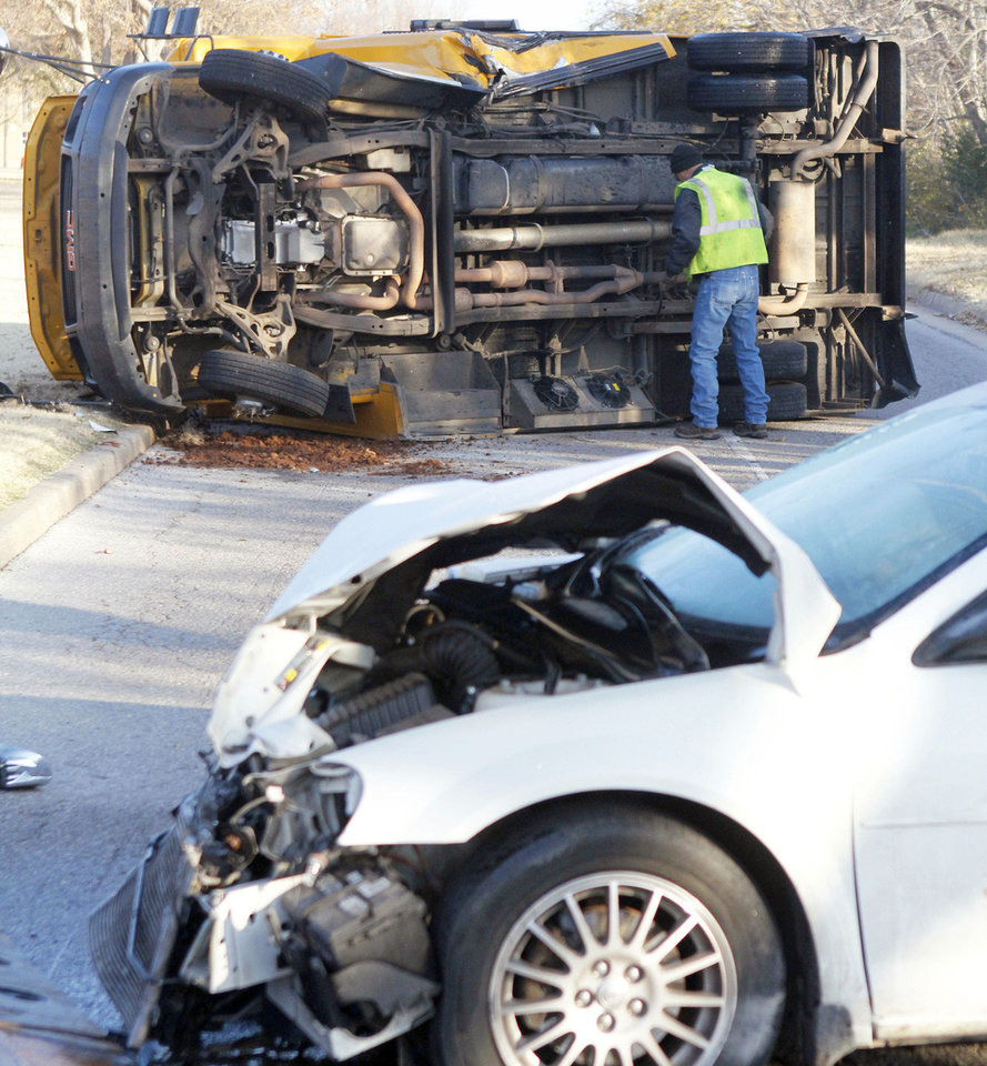 Emergency workers investigate an accident involving an Oklahoma City school bus and an automobile Tuesday morning at the intersection of NW 89 and Classen Boulevard. The driver of the car fled the scene, police said. Photo By Paul Hellstern, The Oklahoman