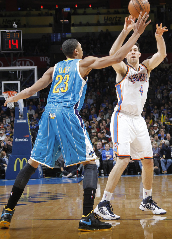 Photo - Oklahoma City Thunder's Nick Collison (4) passes the ball over New Orleans Hornets' Anthony Davis (23) during the NBA basketball game between the Oklahoma CIty Thunder and the New Orleans Hornets at the Chesapeake Energy Arena on Wednesday, Dec. 12, 2012, in Oklahoma City, Okla.   Photo by Chris Landsberger, The Oklahoman