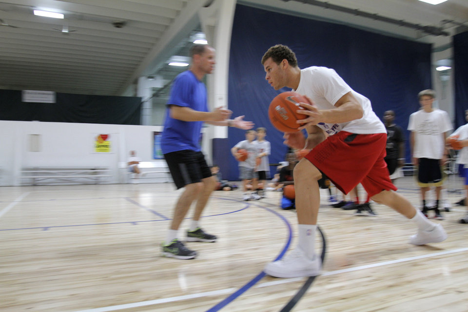 Blake Griffin drives the ball past Mike Moreau during the Blake Griffin basketball camp at the Santa Fe Family Life Center in Oklahoma City Thursday, Aug. 4, 2011. Photo by Garett Fisbeck, The Oklahoman