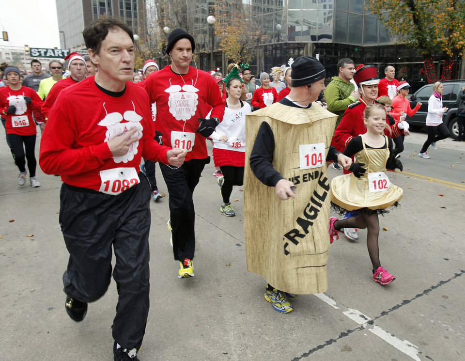 Runners in Christmas costumes begin the SandRidge Santa Run in downtown Oklahoma City, OK, Saturday, December 8, 2012,  By Paul Hellstern, The Oklahoman