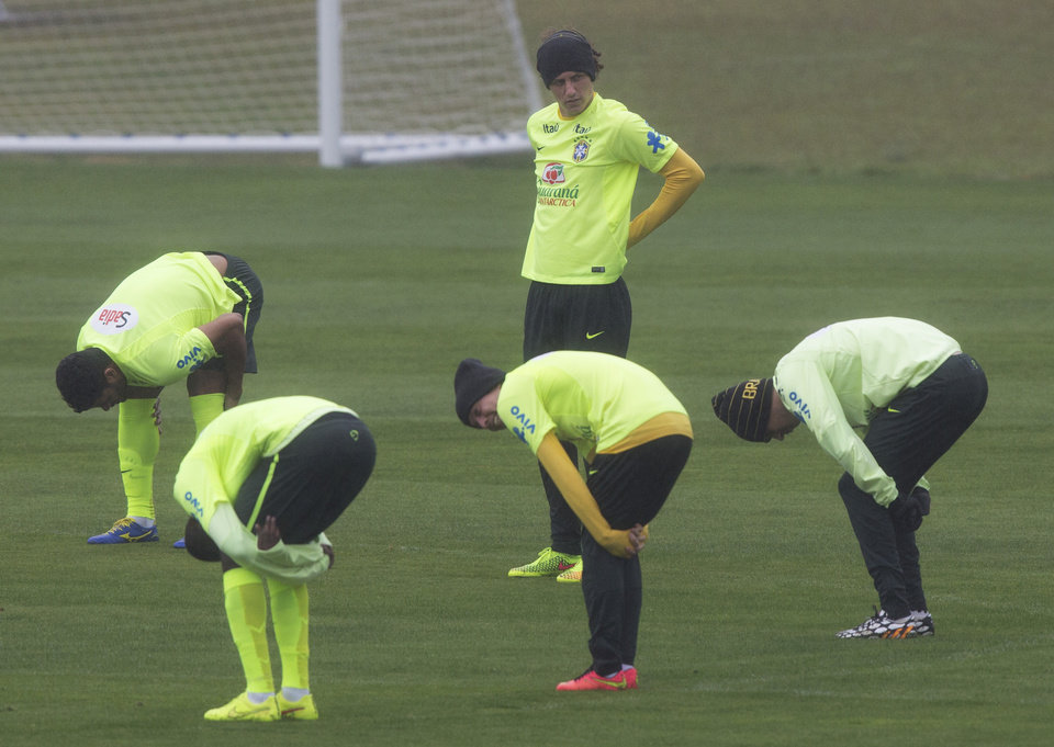 Photo - Brazil's David Luiz stands on the pitch as teammates stretch their muscles during a practice session at the Granja Comary training center in Teresopolis, Brazil, Friday, July 11, 2014. Brazil will face the Netherlands in the World Cup third-place match Saturday. (AP Photo/Leo Correa)