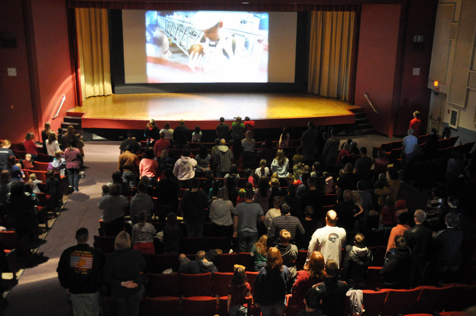 Photo - Some 250 people stand for the playing of the national anthem ahead of a showing of