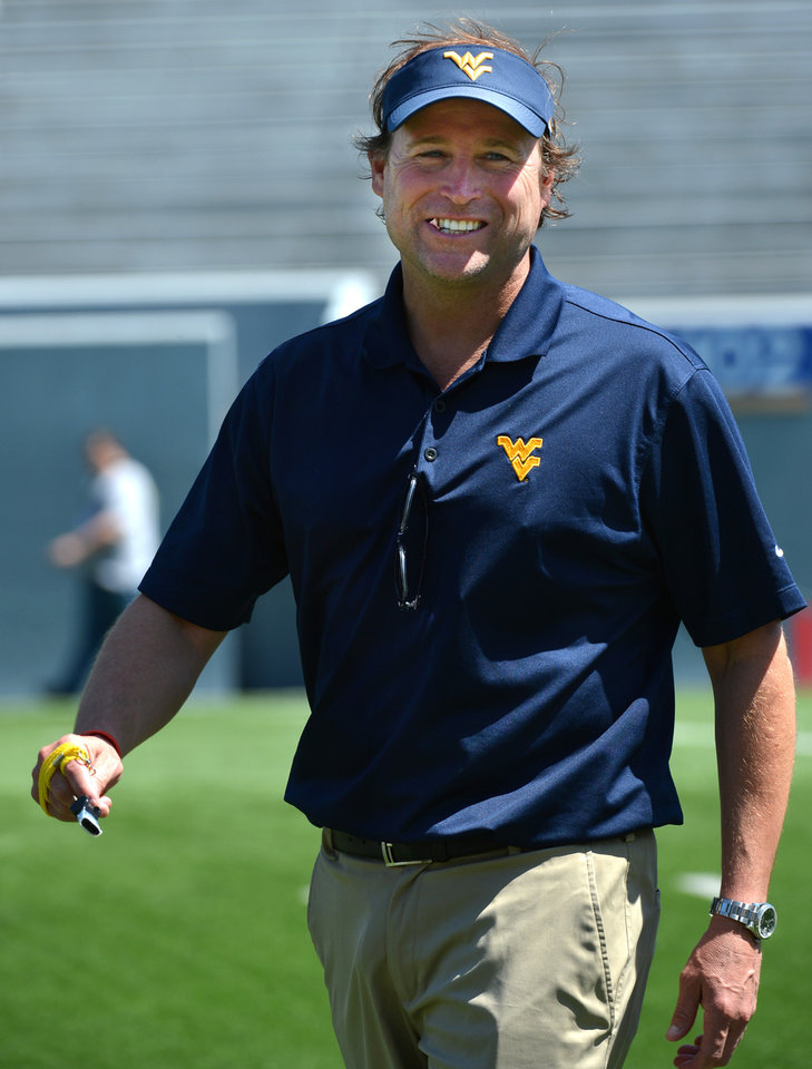 Photo - West Virginia head coach Dana Holgorsen smiles before the start of their spring NCAA college football game in Morgantown, W.Va., Saturday, April 12, 2014. (AP Photo/Craig Cunningham)