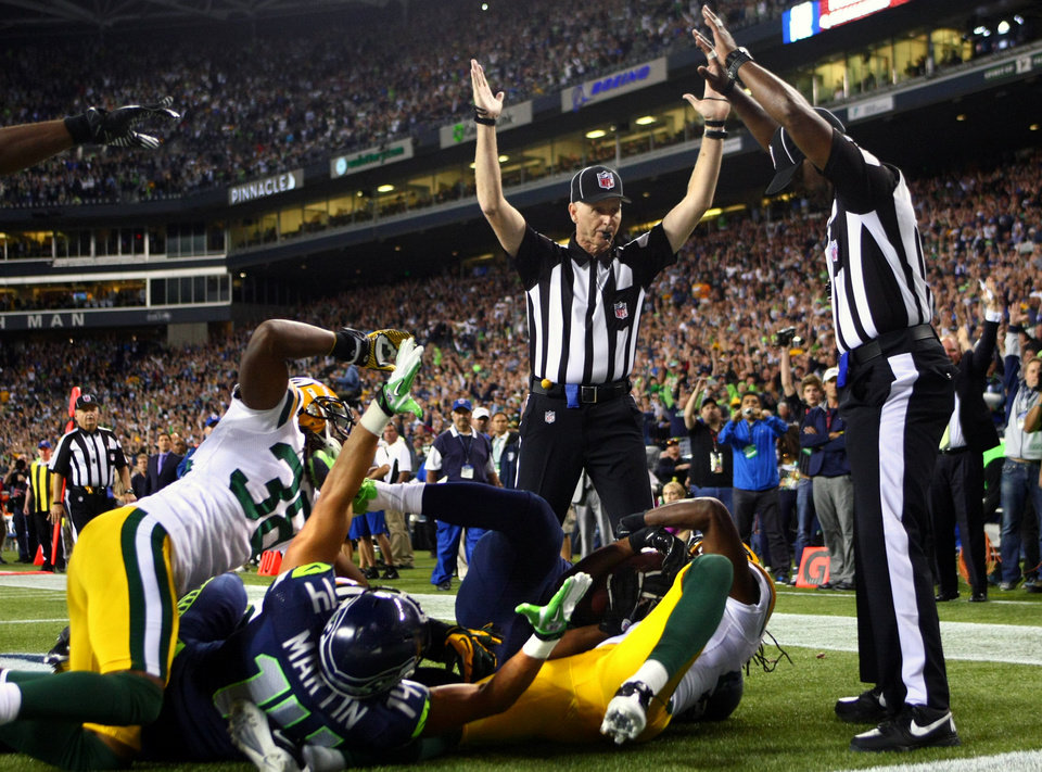 Photo -   Officials signal after Seattle Seahawks wide receiver Golden Tate pulled in a last-second pass for a touchdown from quarterback Russell Wilson to defeat the Green Bay Packers 14-12 in an NFL football game, Monday, Sept. 24, 2012, in Seattle. The touchdown call stood after review. (AP Photo/seattlepi.com, Joshua Trujillo) MAGS OUT; NO SALES; SEATTLE TIMES OUT; TV OUT; MANDATORY CREDIT