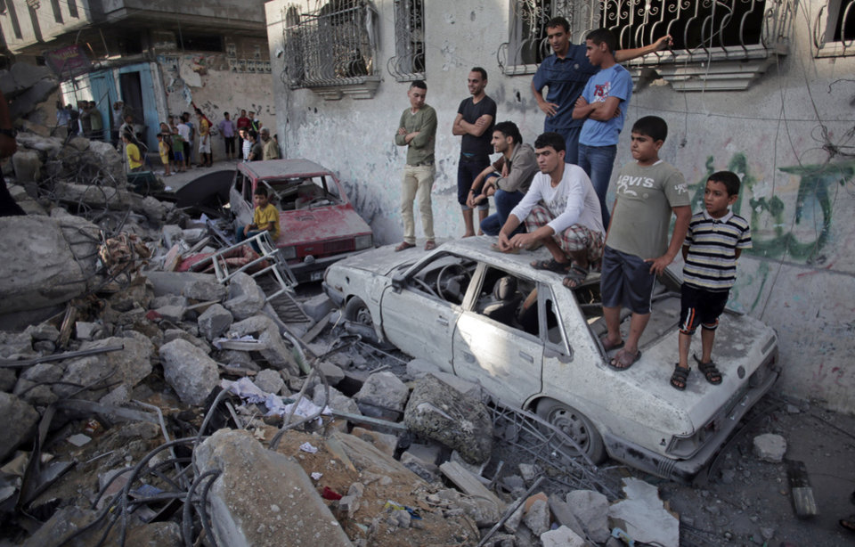 Photo - Palestinians look the damage of a destroyed house where five members of the Ghannam family were killed in an Israeli missile strike early morning in Rafah refugee camp, southern Gaza Strip on Friday, July 11, 2014. Israel launched the Gaza offensive to stop incessant rocket fire that erupted after three Israeli teenagers were kidnapped and killed in the West Bank and a Palestinian teenager was abducted and burned to death in an apparent reprisal attack. The military says it has hit more than 1,100 targets already, mostly what it identified as rocket-launching sites, bombarding the territory on average every five minutes. (AP Photo/Khalil Hamra)