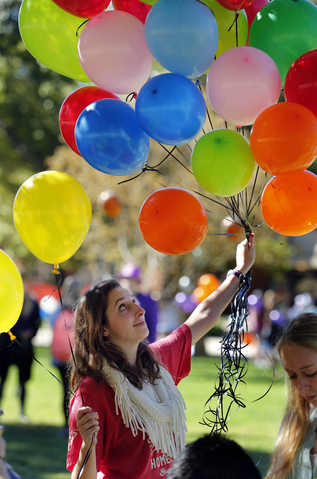 Photo -  University of Oklahoma sophomore Elizabeth McCready, a volunteer with Soonerthon, gets ready to release balloons at a Fill the Oval homecoming philanthropy event on the campus' South Oval. PHOTO BY STEVE SISNEY, THE OKLAHOMAN   STEVE SISNEY -