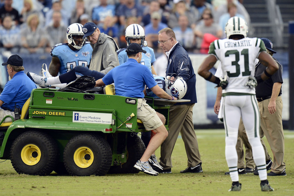 Photo - New York Jets cornerback Antonio Cromartie (31) watches as Tennessee Titans quarterback Jake Locker (10) is taken off the field after being injured in the third quarter of an NFL football game against the New York Jets on Sunday, Sept. 29, 2013, in Nashville, Tenn. (AP Photo/Mark Zaleski)