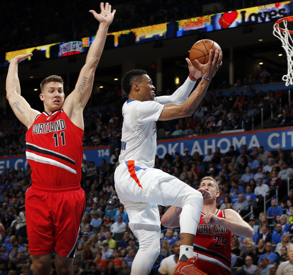Photo - Oklahoma City's Russell Westbrook (0) takes the ball to the basket between Portland's Meyers Leonard (11), left, and Mason Plumlee (24) during an NBA basketball game between the Oklahoma City Thunder and the Portland Trailblazers at the Chesapeake Energy Arena in Oklahoma City, Monday, March 14, 2016. Photo by Nate Billings, The Oklahoman