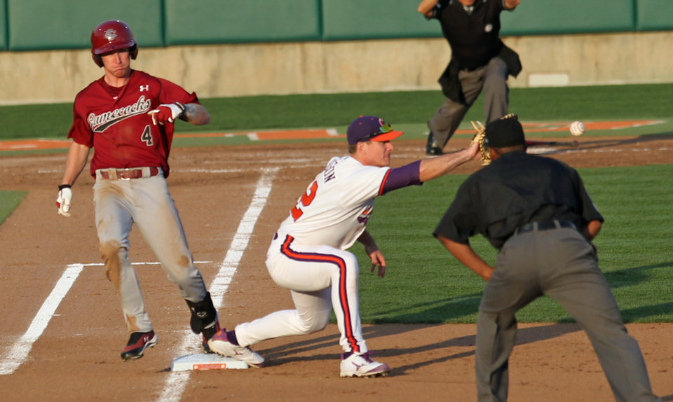 Umpire David Brown, right, watches as South Carolina\'s Connor Bright, left, tags the bag for a single before Clemson first baseman Jon McGibbon catches the ball during an NCAA college baseball game on Sunday, March 2, 2014 in Clemson, S.C. (AP Photo/Anderson Independent-Mail, Mark Crammer) GREENVILLE NEWS OUT SENECA JOURNAL OUT