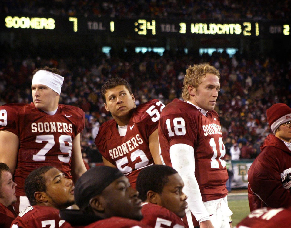 Photo - OU: Trailing 21-7 going into halftime, the University of Oklahoma offense led by quarterback Jason White (18) watch from the sidelines as Kansas State University scored three second quarter touchdowns during the Big 12 college football championship at Arrowhead Stadium in Kansas City, Mo., Saturday, Dec. 6, 2003. At left is Chris Messner (79), Chris Bush (52). (AP Photo/The Dallas Morning News, Tom Fox)