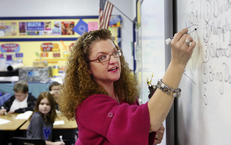 Photo - Sallie Harrison, a fourth-grade science and math teacher at Meeker Elementary School gives a lesson in long division. Harrison has has multiple sclerosis.    Photo by Jim Beckel, The Oklahoman  Jim Beckel - THE OKLAHOMAN