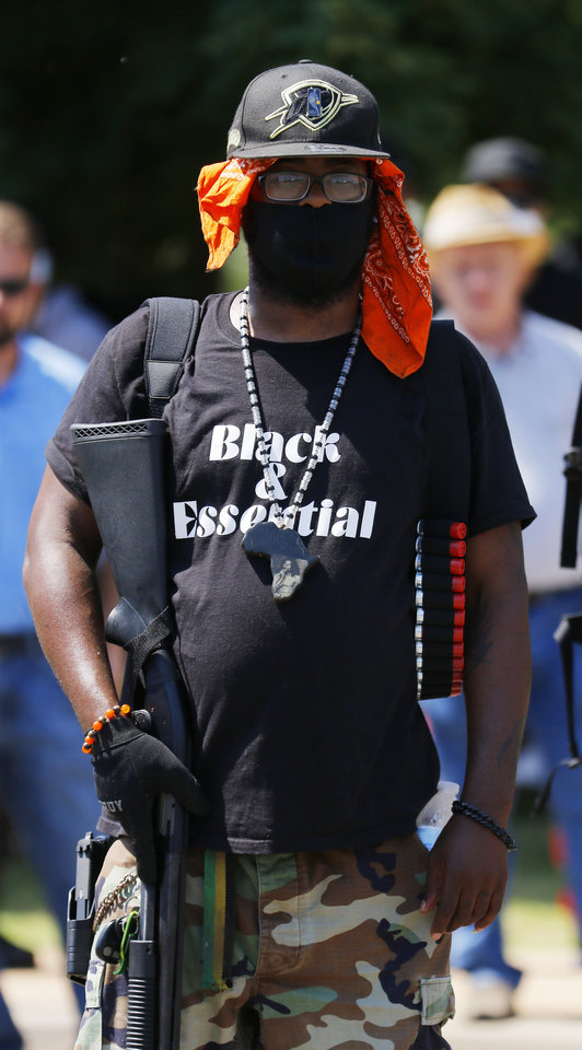 Photo - An armed man listens to a speaker at a 1,000 brothers and sisters in arms for second amendment walk by predominantly black men and women to advocate for their second amendment rights, Saturday, June 20, 2020. [Doug Hoke/The Oklahoman]