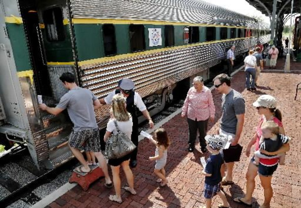 Volunteer conductor Steve Davis assists passengers boarding the chair car for a train trip last year at the Oklahoma Railway Museum. Photo by Jim Beckel, The Oklahoman    <strong></strong>