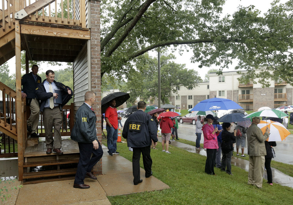 Photo - FBI agents leave an apartment building adjacent to a makeshift memorial for Michael Brown on Saturday, Aug. 16, 2014, located at the site where Brown was shot by police a week ago in Ferguson, Mo. Brown's shooting in the middle of a street following a suspected robbery of a box of cigars from a nearby market has sparked a week of protests, riots and looting in the St. Louis suburb. (AP Photo/Charlie Riedel)