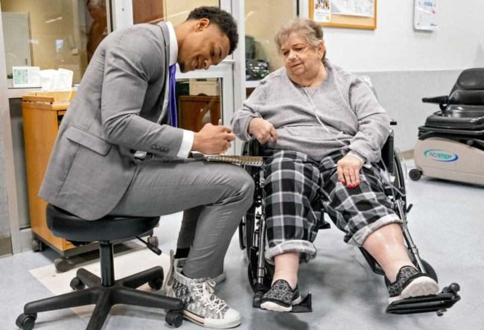 Photo -  LSU defensive back Grant Delpit signs an autograph as he talks with patient Wanda Brinsfield at INTEGRIS Southwest Medical Center's Jim Thorpe Rehabilitation center in Oklahoma City on Tuesday. Delpit visited with patients before accepting the Jim Thorpe Award in the evening. [Chris Landsberger/The Oklahoman]