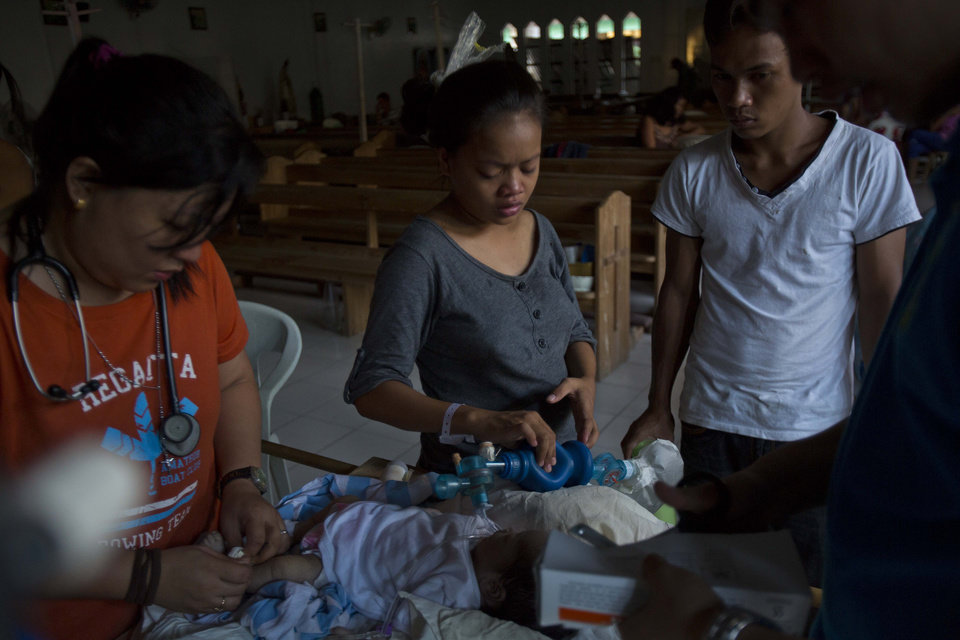 Photo - Genia Mae Mustacisa, center, pumps oxygen into the lungs of her three-day-old infant in front of the altar of a Catholic chapel inside the Eastern Visayas Regional Medical Center in Tacloban on Saturday Nov. 16, 2013. On the right is her husband Emmanuel Barrico. The chapel is now being used to care for infants after Typhoon Haiyan destroyed the original facility of the hospital. (AP Photo/David Guttenfelder)