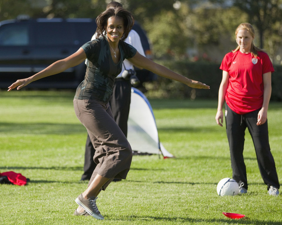 """FILE - In this Oct. 6, 2011, file photo, first lady Michelle Obama plays soccer on the South Lawn of the White House in Washington, as part of a Let's Move! clinic. Michelle Obama has a new look, both in person and online, and with the president's re-election, she has four more years as first lady, too. The first lady is trying to figure out what comes next for this self-described """"mom in chief"""" who also is a champion of healthier eating, an advocate for military families, a fitness buff and the best-selling author of a book about her White House garden. For certain, she'll press ahead with her well-publicized efforts to reduce childhood obesity and rally the country around its service members. (AP Photo/Evan Vucci, File)"""