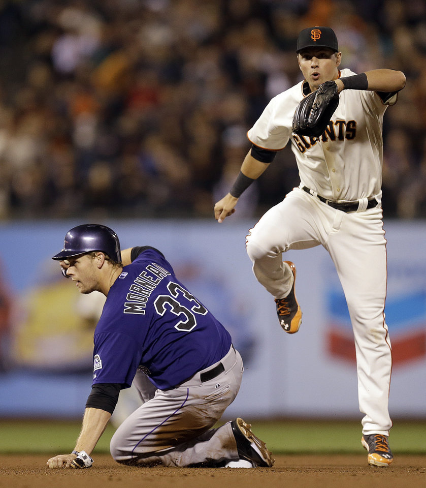Photo - San Francisco Giants' Joe Panik, right, hops over Colorado Rockies' Justin Morneau (33) after completing a double play in the fourth inning of a baseball game Wednesday, Aug. 27, 2014, in San Francisco. Nolan Arenado was out at first base. (AP Photo/Ben Margot)