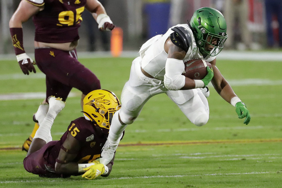 Photo - FILE - In this Nov. 23, 2019, file photo, Oregon running back CJ Verdell, right, is tackled by Arizona State safety Cam Phillips (15) during the first half of an NCAA college football game in Tempe, Ariz. The Ducks will have to replace five starters on the offensive line. But Oregon returns significant skill position players, including running back CJ Verdell. (AP Photo/Matt York, File)