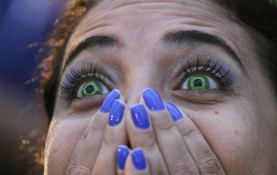 Photo - A Brazil soccer fan wearing contact lenses that mimic the Brazilian flag reacts as she watches her team play Germany in a World Cup semifinal game via live telecast inside the FIFA Fan Fest area on Copacabana beach in Rio de Janeiro, Brazil, Tuesday, July 8, 2014. (AP Photo/Leo Correa)