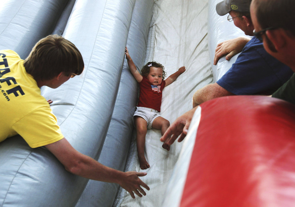 Photo -  Mackenzie Duncan slides down an inflatable at last year's Norman Day celebration in Reaves Park. PHOTO BY K.T. KING, THE OKLAHOMAN ARCHIVES    KT King -