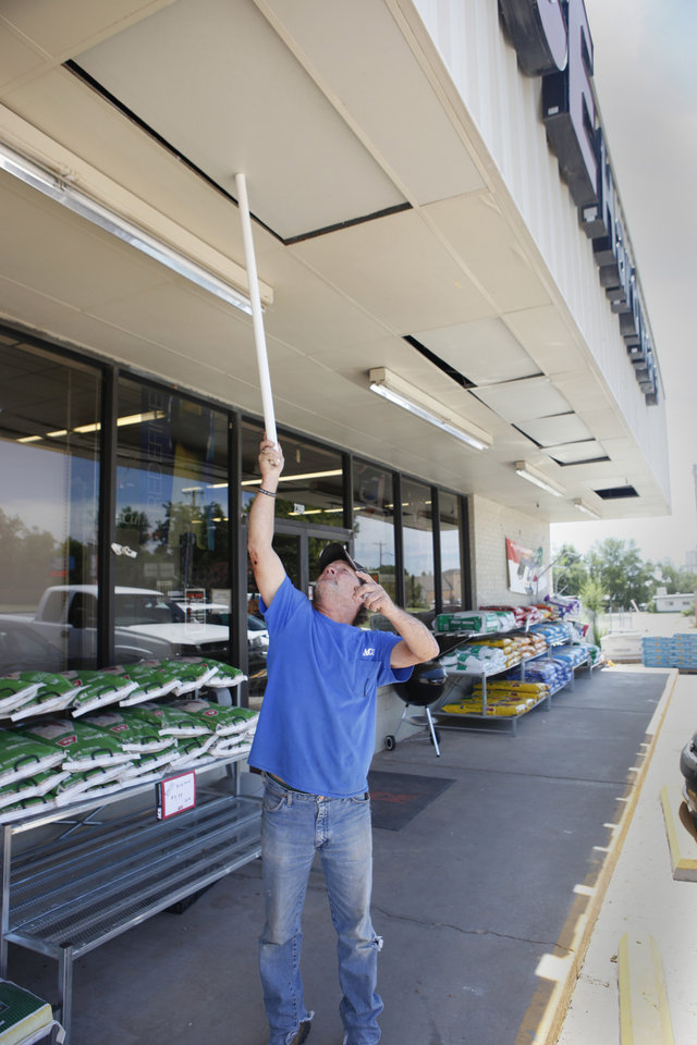 Photo -  Ace Hardware employ Ray Looney uses a PVC pipe to straighten ceiling tiles moved out of place by an early morning earthquake in Harrah on Tuesday. Photo by David McDaniel, The Oklahoman   David McDaniel