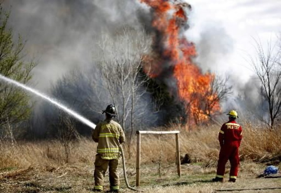 Photo - Firefighters battle a grass fire in a neighborhood near South County Line Road near S.W. 29th, Sunday, March 20, 2011, in Mustang, Okla.. Photo by Sarah Phipps