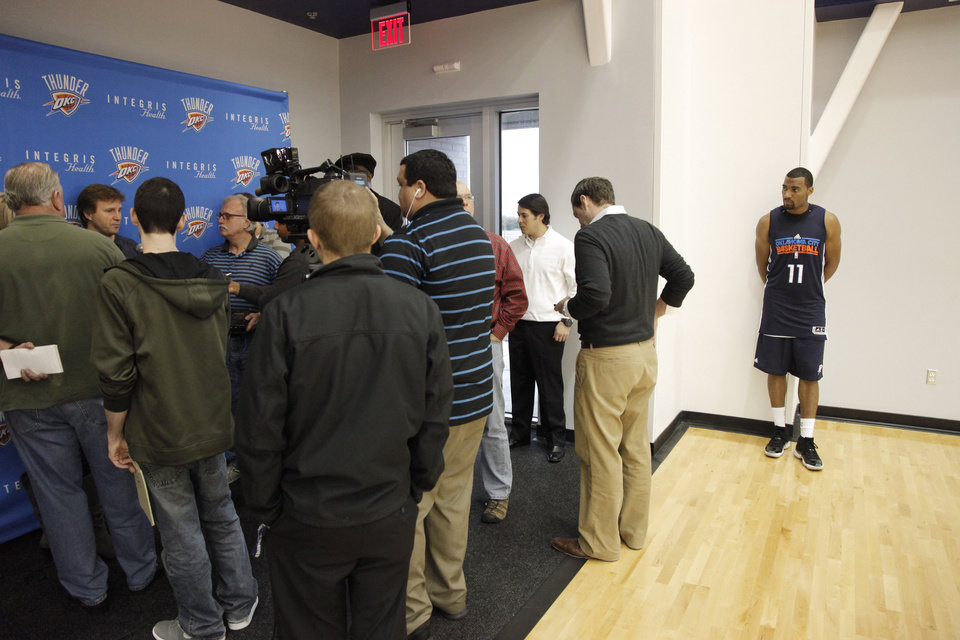 Photo - New Thunder player Lazar Hayward watches as Thunder coach Scott Brooks talks with the media at the end of a practice session at the Thunder Practice Facility, Wednesday, Dec. 14, 2011. Photo by Doug Hoke, The Oklahoman