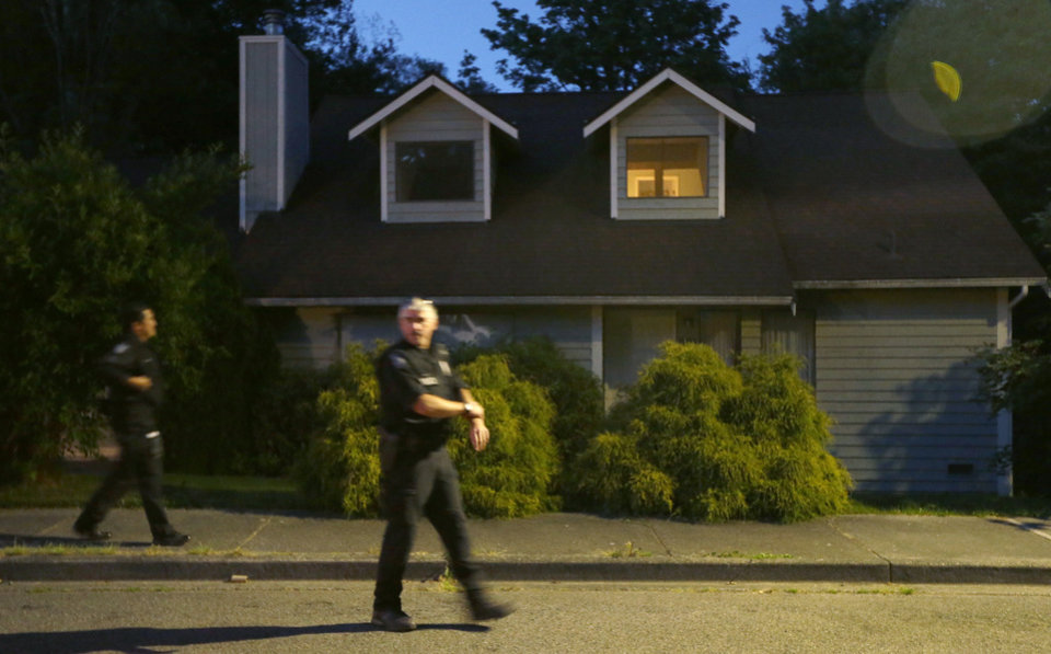 Photo - Seattle Police officers walk past a home believed to be tied to Aaron R. Ybarra, who was arrested Thursday, June 5, 2014 following a shooting at Seattle Pacific University in Seattle. (AP Photo/Ted S. Warren)